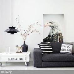 Das Wandbild mit Adlermotiv zieht in diesem Wohnzimmer alle Blicke auf sich. Der Couchtisch im Industrial-Look, die dunkelgraue Couch und die schwarze  …