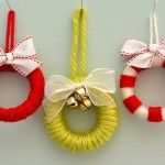 Miniature Wreath Ornaments using plastic shower curtain rings, yarn, and ribbon.