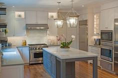 Pine Street Carpenters & The Kitchen Studio at Pine Street adds dimension to this kitchen by choosing a rich grey paint for the island base and white cabinets topped with Pebble around the perimeter. The result is glamorous and inviting space.