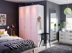 Een grote slaapkamer met een witte kast met lichtroze deuren in combinatie met een bed en commode, zowel in het wit.