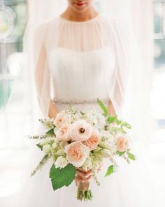 """Garden roses, ranunculus, and blushing bride proteas kept the bouquet by McKenzie Powell """"a little bit wild,"""" Bomi says."""