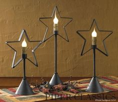 "Star Candlestick Lamp - 17"" from Park Designs has a metal star shape on a candlestick base. Silicone bulb sold separately .Twinkling starlight shines from the center of the star, brightening any small area. Electric. Made of metal and finished in distressed black, this lamp stands 17"" tall. Base measures 4"" in diameter (Shown center.) #holiday decor"