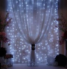 Strings of mini-lights attached to a rod behind sheer fabric.