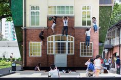 Visitors are reflected in a mirror while sitting on the installation of the Argentine Leandro Erlich, entitled Batiment - Oi!
