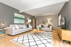large family room, grey and white walls, geometric woven floor rug, neutral sofa, cream and blue cushions, timber tv cabinet and console table, blue green and white canvas painting,