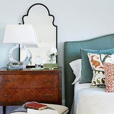 MIRROR NEXT TO BED -- Mirrors perform several important functions in a bedroom. They let you check your appearance before you head out the door in the morning. They also bounce light—daylight or lamplight—around a space, which can make a dark bedroom brighter and livelier. If the mirror above a bed faces a blank wall or something rather drab, hang it at a slight angle, tilted out from the wall and it will reflect the colorful bedding below instead.