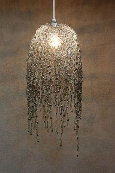 """Questo lampadario, di ispirazione leggermente """"dark"""" , è un originale modo per riciclare le spille da balia. Certo, ve ne occorreranno tantissime e tanta pazienza per incatenarle fra loro, ma il risultato è sicuramente sorprendente. Come base, utilizzate la rete di fil di ferro."""