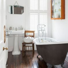 All-white bathroom with roll-top bath and shutters Dark Floor Bathroom, White Bathroom Cabinets, Wooden Bathroom, Bathroom Flooring, Small Bathroom, Neutral Bathroom, Light Bathroom, Attic Bathroom, Basement Bathroom