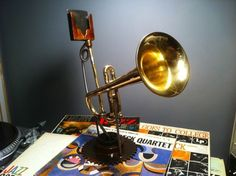 #Iphone, #Ipod, #Music This device was made from a salvaged trumpet and assorted machine parts. The base is steel, the legs that hold everything up are stainless steel, and the cradle that holds the telephone is also steel. The horn is brass. All of the steel has been