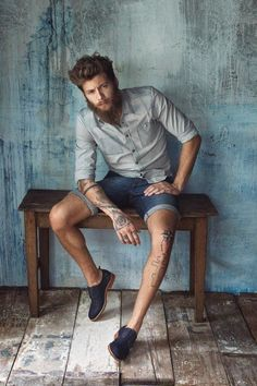 Mens fashion / mens style - denim shorts and open tan shirt with tats.