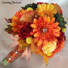 Vibrant, autumn bouquet of realistic artificial florals by Something Spectacular/Something Floral containing orange calla lilies, red and yellow roses, orange and gold gerbera daisies, green succulents, gold pods, and crystals, encircled by a base of autumn leaves, and stems wrapped in burnt sienna and metallic copper ribbon. #wedding #bouquet #bridal #bridesmaid #autumn #succulents #calla #lily #lilies #gerbera #daisy #daisies #fall