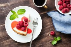 Cheesecake with raspberries and berry sauce on wooden table by Berry Sauce, Omelette, Wooden Tables, Fun Desserts, Waffles, Raspberry, Cheesecake, Spices, Breakfast