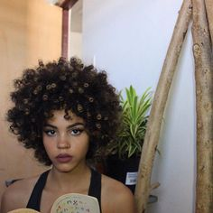 Short, natural curls with light golden highlights.