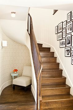 source: Mona Ross Berman Interiors  Under the stairs reading nook features Kelly Wearstler Imperial Trellis Sand/Ivory as well as linen slipper chair paired with blue lacquered accent table over chocolate wood floors. Foyer features black and white photo wall on curved staircase