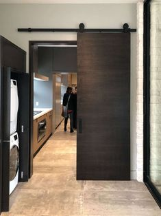 This dark stained wood barn door makes a statement in this modern, contemporary style home. Wood Barn Door, Barn Doors, Light Paint Colors, Craftsman Style Doors, Dark Wood Stain, Small Hallways, Spacious Living Room, Beautiful Bedrooms, White Trim