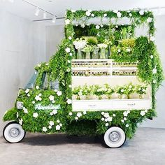 """A Piaggio Ape Covered in Green and Converted Into a Flower Shop"" on Spoon & Tamago. This adorable setup is selling flowers at the Ginza flagship store of Italian luxury brand Fendi."