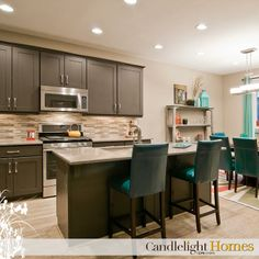 www.CandlelightHomes.com, kitchen, black cupboards, can lights, lighting, turquoise bar stools, wooden floors, wood flooring, stainless steel appliances, backsplash, interior design, kitchen design, candlelight homes