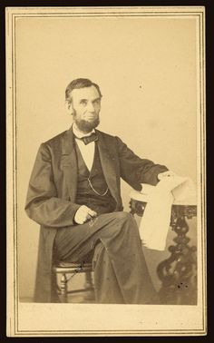 Abraham Lincoln, U.S. President. Seated portrait, holding glasses and newspaper, Aug. 9, 1863