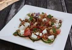 Salad from zucchini, tomato, cheese and nuts vinaigrette