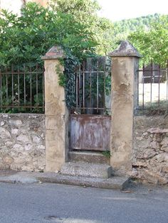 This style of gate, in southern France, is appropriate for use in a town.  The solid base to the gate prevents litter from entering the garden.