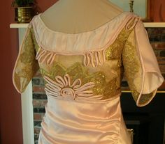 The bodice of the 1909 evening gown, showing hand-applied pink silk satin rouleaux trim and details of metallic gold net and lace overbodice. The silk chiffon guimpe was finished with an edging of natural freshwater pearls along the neckline, and pink pearls and clear Swarovski crystals were applied as accents on the overbodice.