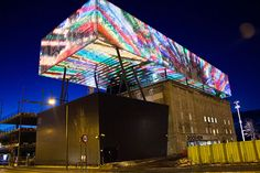 "Generative video for LED media facade of Rockheim (Norway's national museum of pop and rock), Trondheim. The facade is relatively lo-res, but wraps around the ""box"" in all directions with varying pixel density. ByMarius Watz"