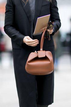 Grey top, black classy coat and tan modern bag.
