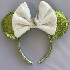 Tinkerbell Minnie Ears are perfect for your day spent at the most magical place on Earth! Perfect for any Peter Pan or Tinkerbell enthusiast or an Tinkerbell-themed DisneyBound outfit. Please note these are offered in two styles: - Without Tink - With Tink Sitting on Bow (additional $2.50)