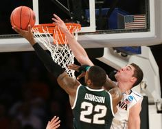 Branden Dawson scores past Virginia's Joe Harris during the second half of a regional semifinal at the NCAA men's college basketball tournament, Friday, March 28, 2014, in New York. (AP Photo/Seth Wenig)