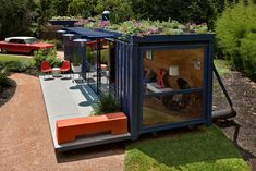 shipping container studio— complete with a rooftop garden that adds extra color to the navy exterior and orange accent pieces.