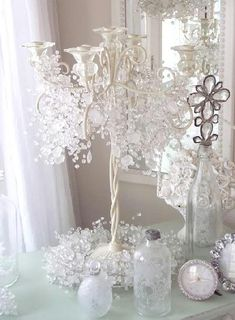 Play around with beaded or floral garland and a candelabra. This clear-beaded garland looks like ice both weaved around the top of the candelabra and around the base. This makes a beautiful centerpiece for any winter event. Add other white or clear pieces to increase the size of your centerpiece.