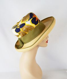 Very high crown, much like the mad hatter, crafted in a navy blue, cream, red, yellow and brown leaf fabric, 2 1/4 inch wide moss green
