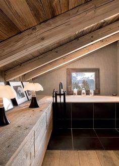 Dans cette salle de bain sous les toits du chalet, je suis sous le charme des mini lampe pipistrello et de la baignoire encastrée noire