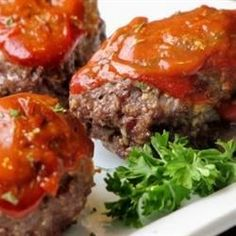 A meatloaf mixture of ground beef, cheese, and quick-cooking oats is formed into individually sized loaves. They are glazed with a sauce of ketchup, brown sugar, and mustard.