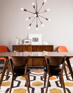 Dining Room decor ideas - midcentury modern style in orange & yellow with sputnik chandelier, all wood table and chairs, Eames side chairs and brown, mustard and tangerine 70's inspired patterned rug.