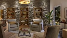 contemporary stone wall, built-in bookcases, neutral color palette, home library, home office, study