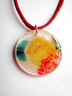 Resin Pendant Necklace MultiColored Flowers and Butterfly Resin Pendant on Sienna Suede with Sterling Clasp, via Etsy.