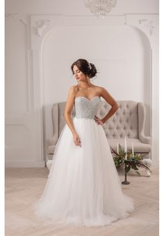 This dazzling ball gown features an exquisitely crafted handsewn crystal corset, a flowing tulle organza, and a classic sweetheart neckline