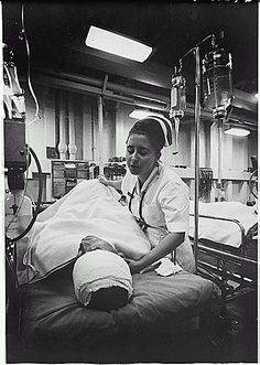 A nurse tends to her patient aboard the hospital ship USS Repose, October 1967. U.S. Navy photograph.