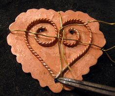 Love Never Fails Necklace    To solder the copper filigree wire in place, I hold it down with scrap brass wire. Then I place chips of solder at the points where I'd like the filigree to become connected to the copper sheet.
