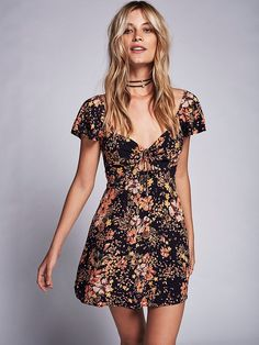 The Coolest Mini Dress | Retro-inspired floral mini dress with a cutout at the underbust in front and back and an adjustable tie with smocked detailing. Super femme flutter sleeves and pleating on the flowy skirt with delicate buttons in back and a hidden back zip closure.