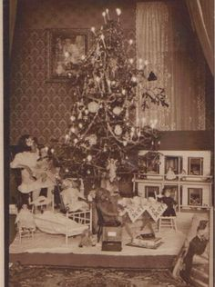 A little girl sitting beside this Christmas tree with a baby doll on her lap, baby dolls on chairs, dolly bed and huge dollhouse