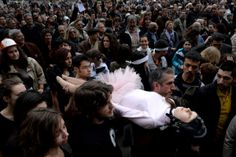 Dimitar Dilkoff - AFP/Getty Images:  Nov. 1, 2013. Some amateur performers of the theater group of Sofia's University carry a protestor wearing a ballet dancer costume as they demonstrate with Bulgaria's students in front of the school.