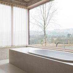 A bath is located in one of the bedrooms inside John Pawson's Life House, in front of a large window that offers views of the surrounding Welsh valley countryside.