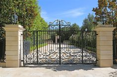 Decorative wrought-iron gates open to the parklike grounds.