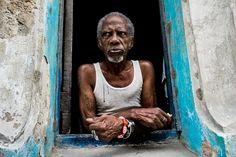 A Palo Monte priest looks out of the window in Havana, Cuba.
