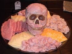 Meat and cheese tray with skull...place thin ham slices on a skull for realistic effect.  Place a black baskets of rolls nearby to make your own sandwiches.  Good idea!