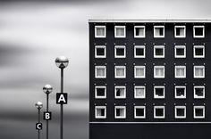 正方形の窓が規則的なリズム感を生んでいる中層ビルと駐車場のランプを主題とし、歪みのないフラットな表現を試みた。NDフィルターで雲を動かして主題を際立たせた。ニコンD700 / タムロン SP 70-300mm F/4-5.6 Di VC USD / 230mm / マニュアル露出(F8、305秒) / ISO 200/ WB:オート