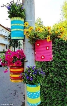 Cute way to dress up a boring pole with plants, flowers and painted cans