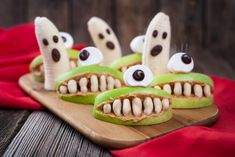 Funny halloween eadible monsters scary food healthy vegetarian snack dessert recipe for party decoration. Homemade spooky cyclop apples with teeth and banana ghosts on vintage wooden background Halloween Snacks For Kids, Halloween Treats For Kids, Halloween Candy, Funny Halloween, Halloween Parties, Costume Halloween, Childrens Halloween Party, Halloween Tips, Halloween Menu
